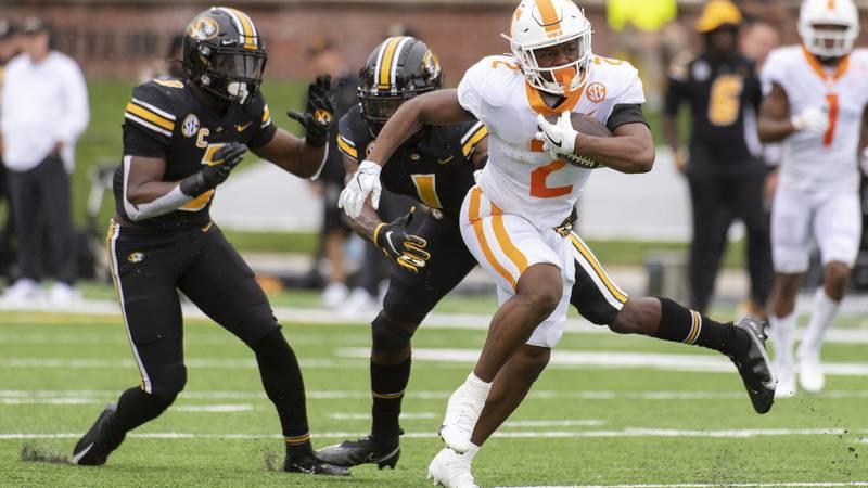 Tennessee running back Jabari Small, right, runs past Missouri's Jaylon Carlies, center, and...