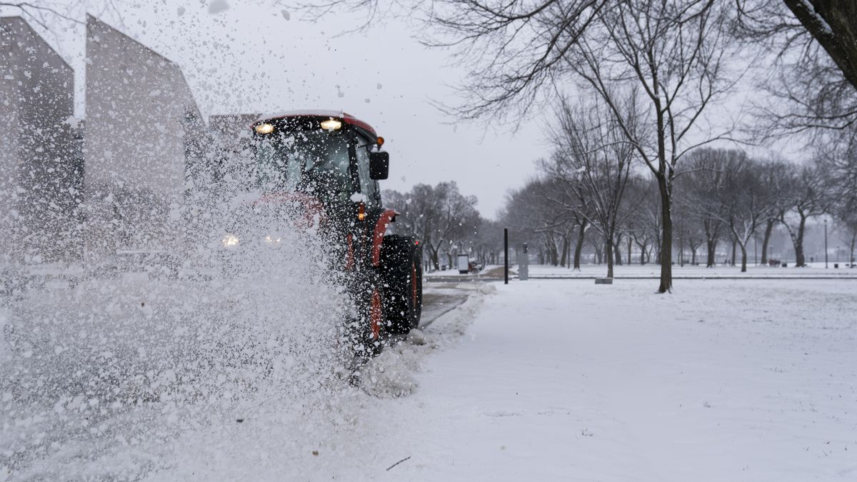 A machine is used to brush snow off the sidewalk on the National Mall, Sunday, Jan. 31, 2021,...