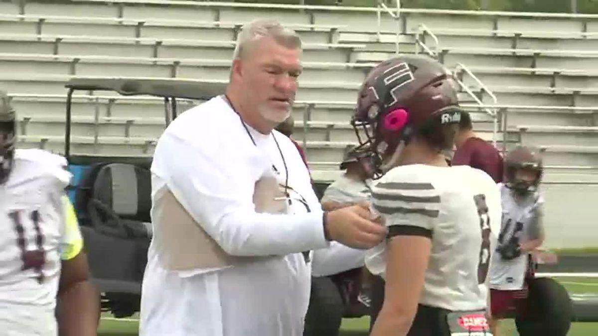 Coach Rob Black adjust shoulder pads as area teams get down hitting