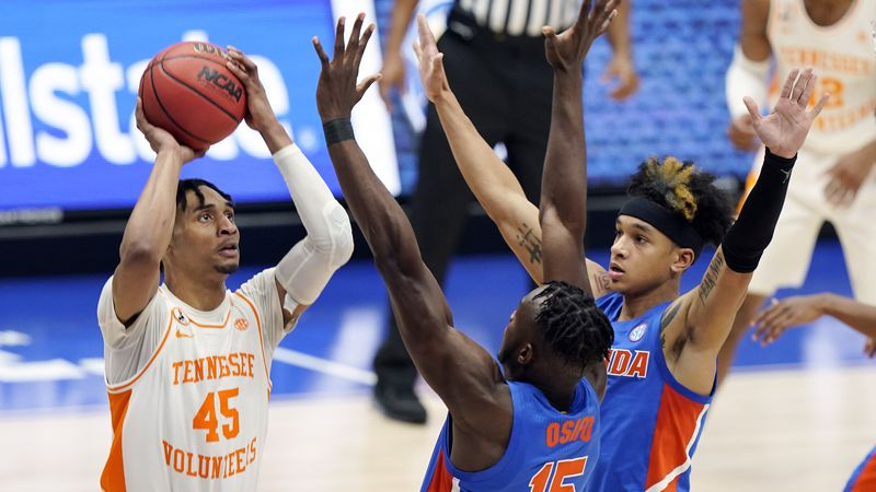 Tennessee's Keon Johnson (45) shoots against Florida's Osayi Osifo (15) and Tre Mann (1) in the...