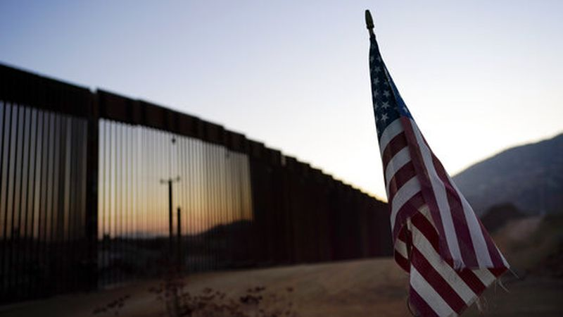A flag sits just north of a new section of the border structure, behind, Thursday, Sept. 24,...
