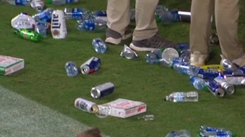 Water bottles, beer cans, golf balls, and a mustard bottle seen thrown onto field