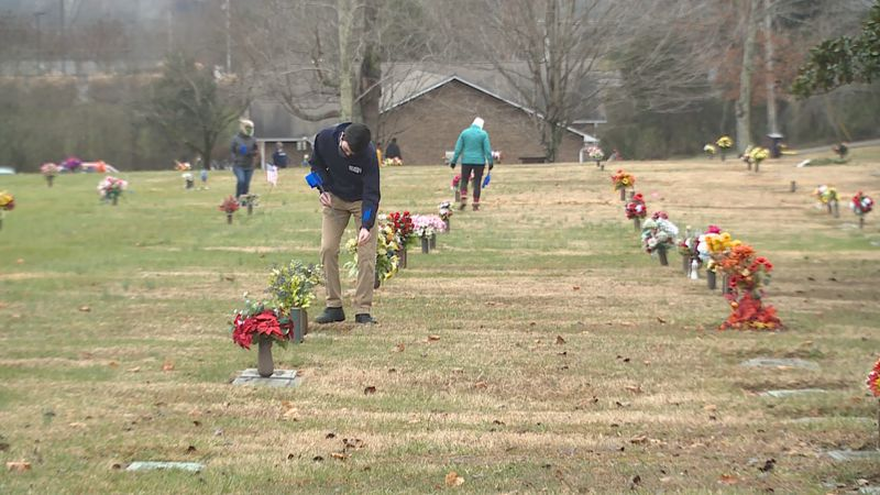 JROTC cadet placed blue flag to mark grave for a wreath to be placed