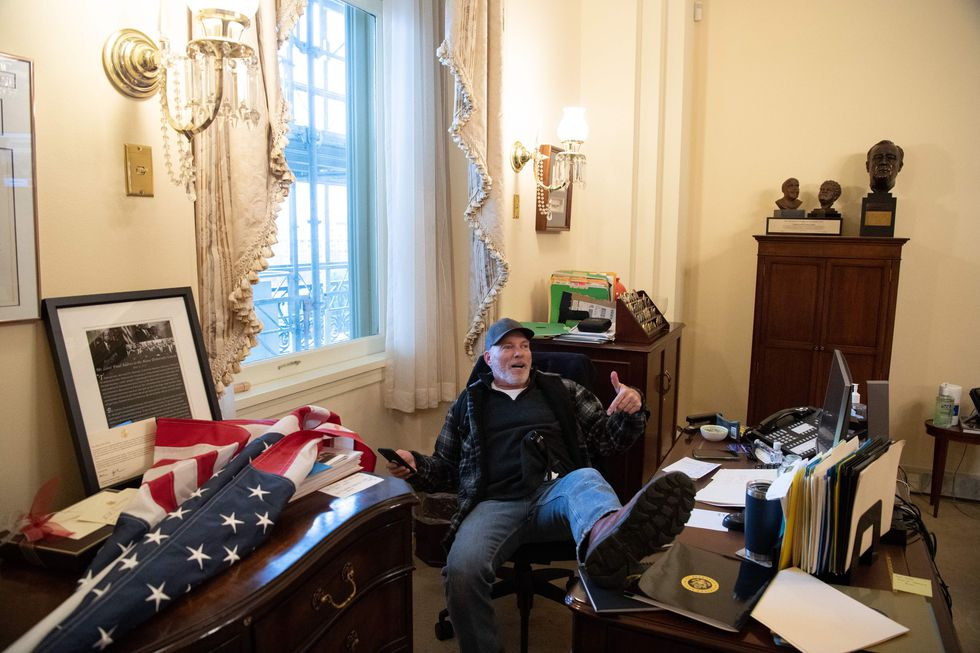 TOPSHOT - Richard Barnett, a supporter of US President Donald Trump sits inside the office of...