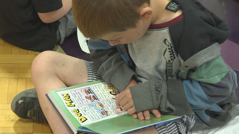 Student reads a book he got for free from the Scholastic Summer Reading Program