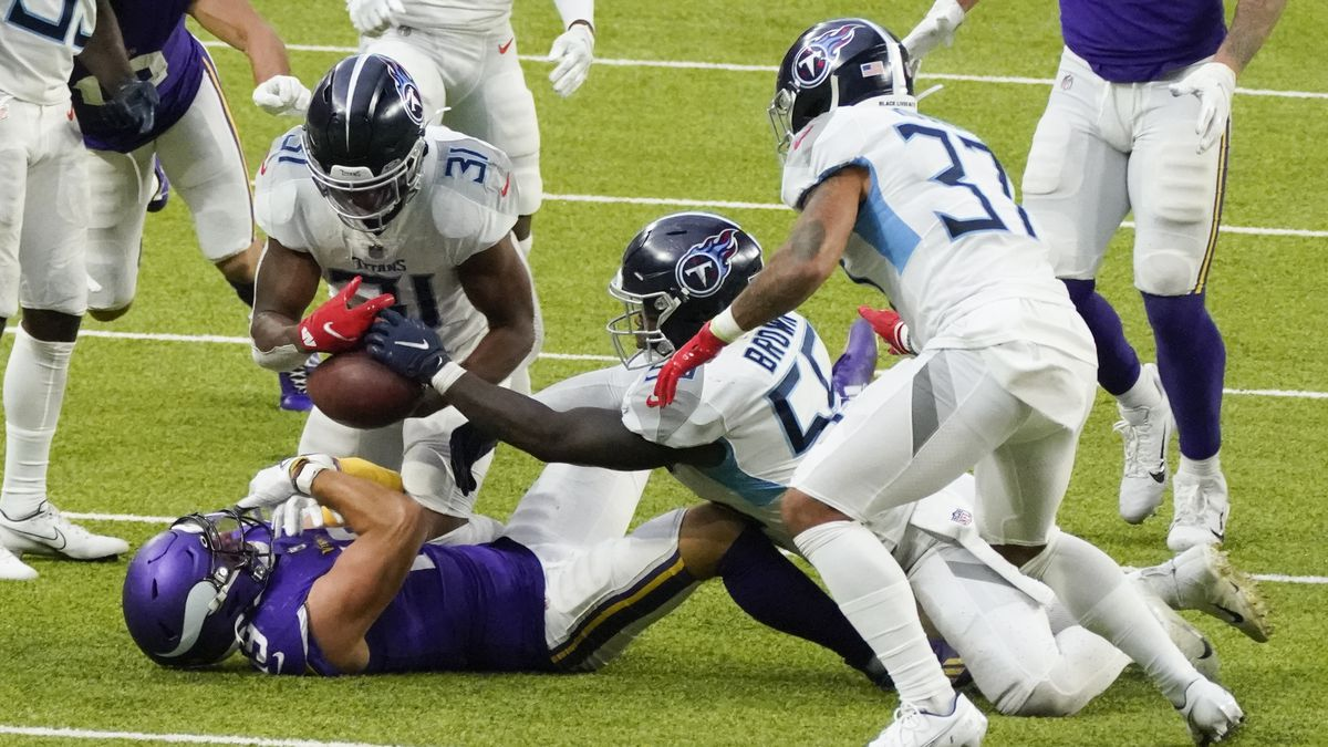 Tennessee Titans free safety Kevin Byard (31), inside linebacker Jayon Brown (55) and safety Amani Hooker (37) strip the ball from Minnesota Vikings wide receiver Adam Thielen during the second half of an NFL football game, Sunday, Sept. 27, 2020, in Minneapolis.