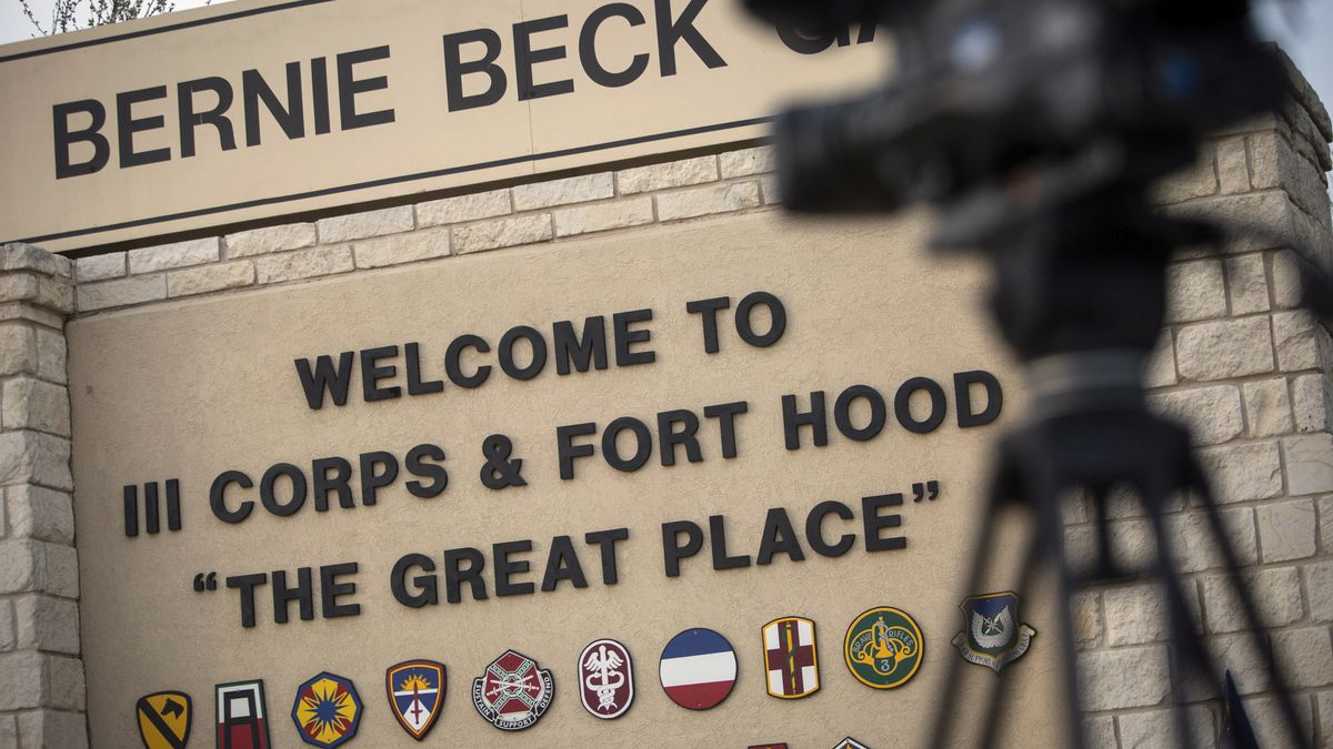 FILE - In this April 2, 2014, file photo, members of the media wait outside of the Bernie Beck Gate, an entrance to the Fort Hood military base in Fort Hood, Texas. Federal agents have seized more than 20 vehicles and the money in 10 bank accounts from a couple of U.S. Army veterans in Texas, who they say used personal information stolen from soldiers to defraud the military out of as much as $11 million. In an affidavit filed in court in June 2020 seeking to search the couple's home in Killeen, near Fort Hood, investigators described how they allegedly used a transportation reimbursement program to swindle the Army out of $2.3 million to $11.3 million.