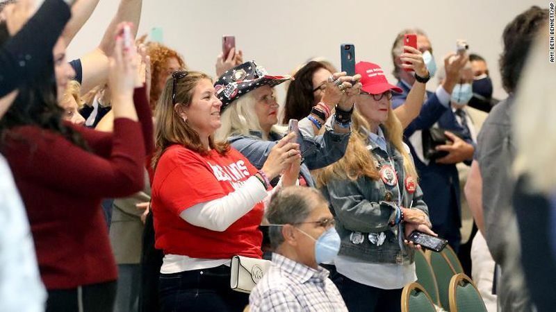 A mostly unmasked crowd cheers and photographs Governor Ron DeSantis as he enters the room to...