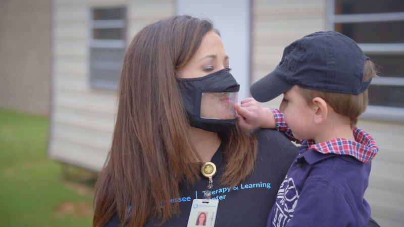 Caregiver worked with child while wearing a clear mask