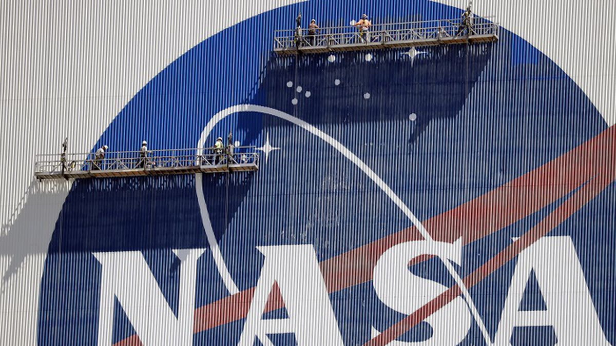 Workers near the top of the 526 ft. Vehicle Assembly Building at the Kennedy Space Center...