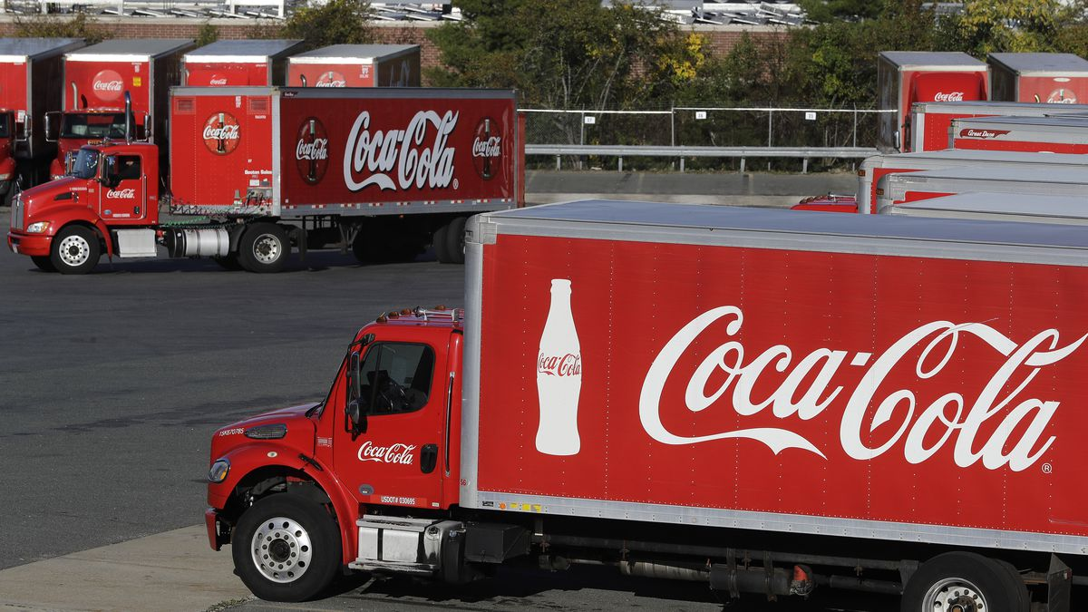 FILE - In this Oct. 14, 2019 file photo a truck with the Coca-Cola logo, behind left, maneuvers in a parking lot at a bottling plant in Needham, Mass.
