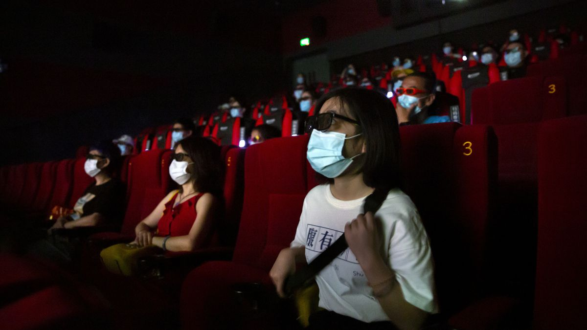 "People wearing face masks to protect against the coronavirus sit spaced apart as they watch the film ""Dolittle"" at a movie theater in Beijing, Friday, July 24, 2020. Beijing partially reopened movie theaters Friday as the threat from the coronavirus continues to recede in China's capital."