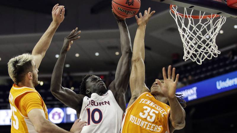 Auburn forward JT Thor (10) puts up a shot as Tennessee guard Yves Pons (35) and Tennessee...