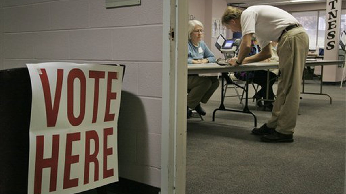 George Collier, right, signs in to vote at a polling place in the wellness and fitness center...