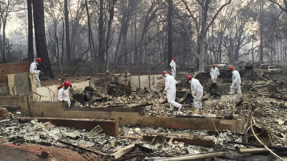In this Nov. 15, 2018 file photo, volunteer rescue workers search for human remains in the...