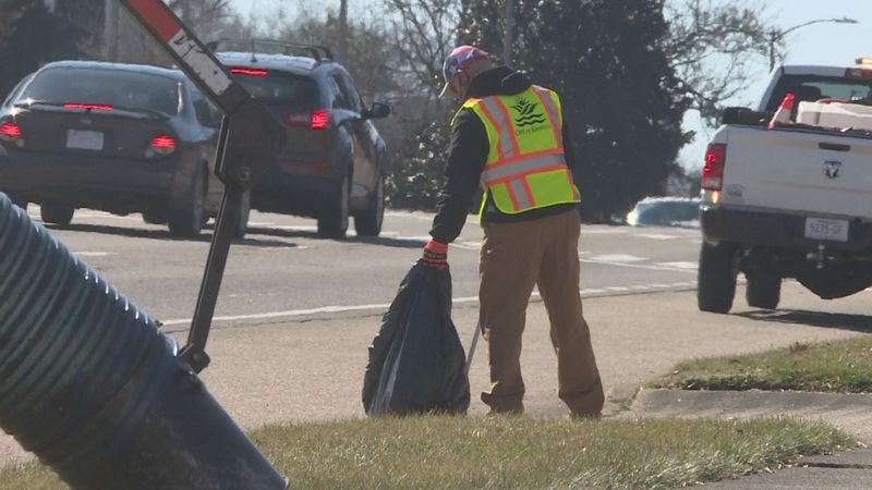 A City of Knoxville employee picks on roadside trash.