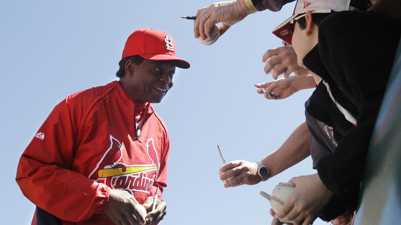 St. Louis Cardinals Hall of Famer Lou Brock signs autographs before a spring training baseball...