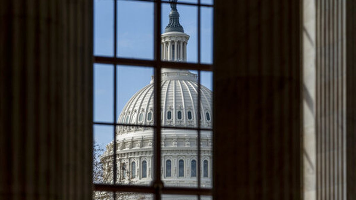 The Capitol is framed through a window in the Russell Senate Office Building as lawmakers...