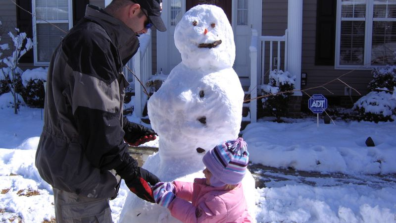 A father and daughter build a snowman.