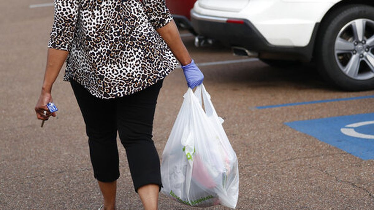 A gloved shopper carries her purchases through the Target parking lot in northeast Jackson, Miss., Wednesday, April 8, 2020. African Americans in Mississippi are being disproportionately affected by the new coronavirus, and many have underlying health problems that make them more vulnerable to it, the state epidemiologist said Tuesday. (AP Photo/Rogelio V. Solis)