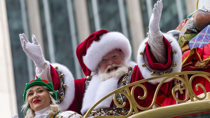 Santa Claus waves in front of Radio City Music Hall on Sixth Avenue during the Macy's...