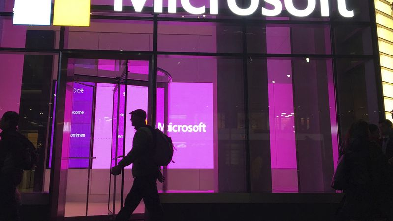 In this Nov. 10, 2016, file photo, people walk past a Microsoft office in New York. China-based...