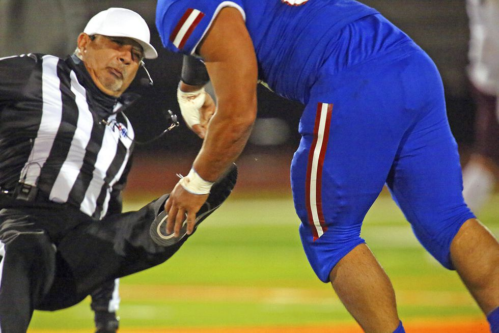 Football referee Fred Garcia falls to the turf after being charged by Edinburg's Emmanuel Duron...