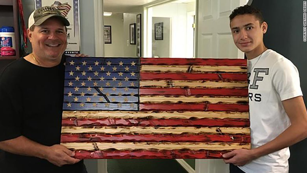 Lorenzo Liberti, 15, with a wooden flag he carved and painted.