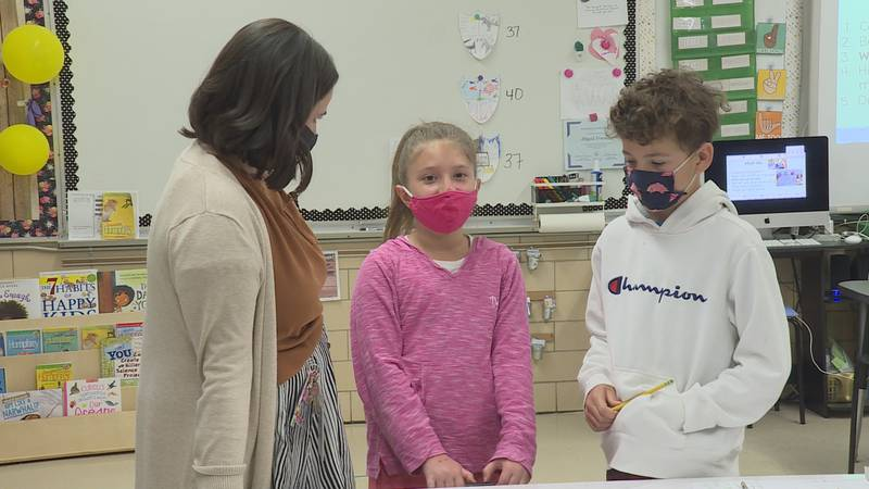 Abby Freeman talks with a couple students about their board game design