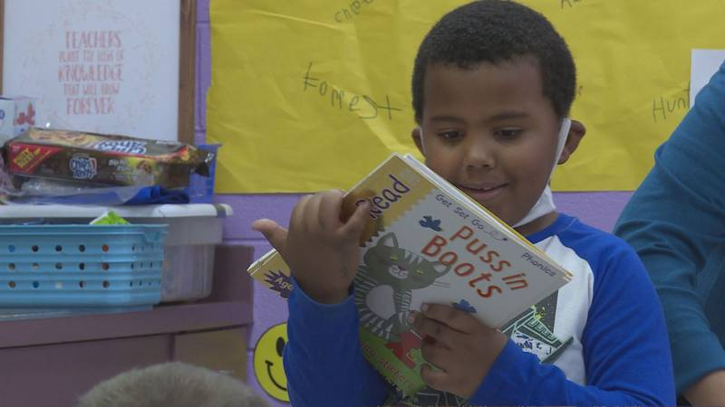 Kindergarten student checks out one of his new books