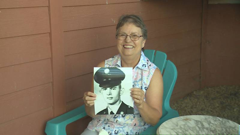 Linda Jennings holds up a picture of Hobert in his Army uniform from the 1960s