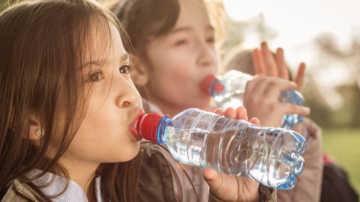 Photo of two girls drinking water from PET bottle.