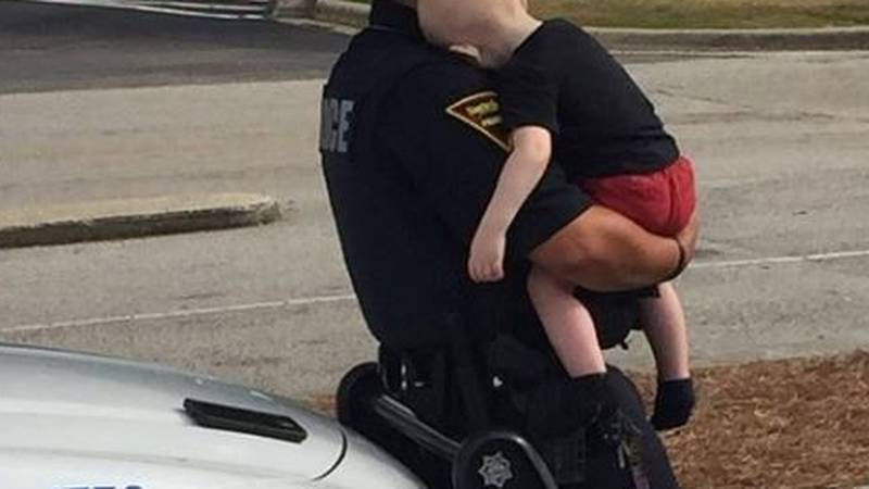 Fayetteville Police Department officer consoles toddler